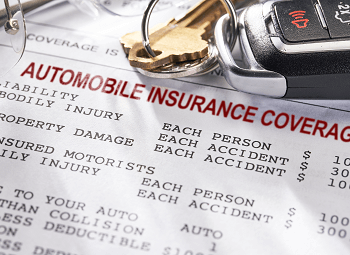 a set of car keys on top of a form that reads automobile insurance coverage